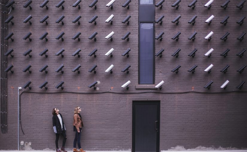 Women looking at a wall full of security cameras