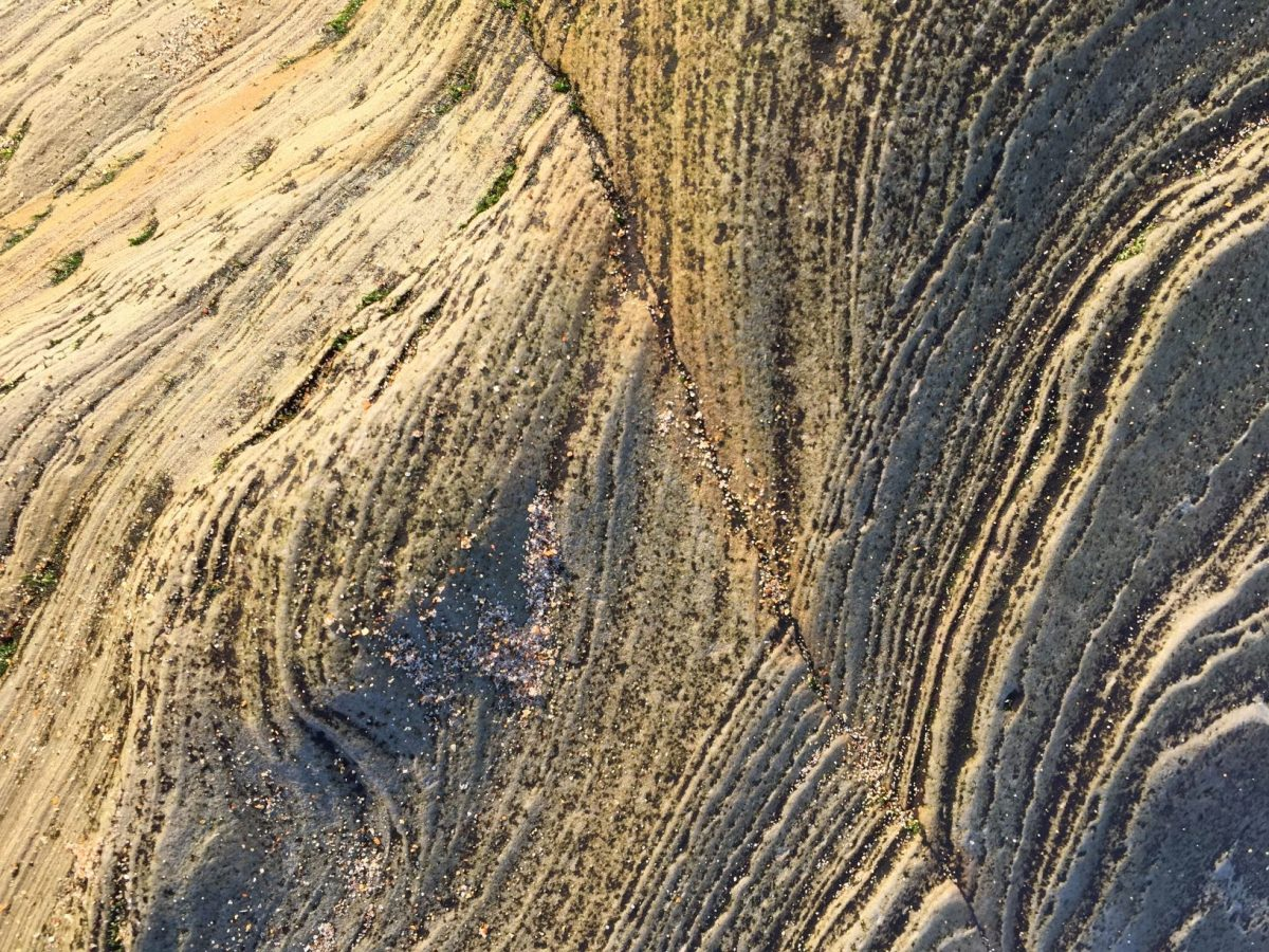 Close up of layered, eroded rock in low sunshine
